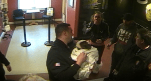 Megan Vitale (second from left) reacts as her puppy, Bodhi, is revived by police officers and firefighters. (North Reading Police Department Surveillance Image)