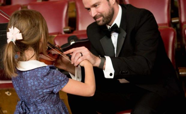 Melrose Schools Orchestra Director Luke Miller, seen here assisting a young student with the violin,has been named the state'sOrchestra Director of the Year. (Courtesy Photo/Melrose Symphony Orchestra)